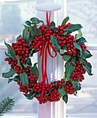 Wreath from Ilex hung on window cross