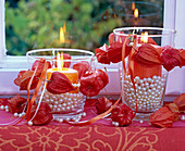 Small physalis wreaths around lanterns filled with pearls