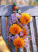 Bouquet of dahlia and aster hanging on wooden chair
