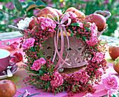 Erica and Dianthus wreath in basket with Malus