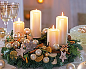 Advent wreath with white candles, balls, stars, slices of orange and cinnamon sticks