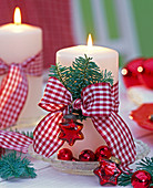 Abies branches with red and white checkered ribbon on white candle