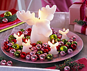 Big and small white moose candles on pink