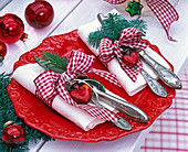 Abies branches on white napkins with red checkered ribbons
