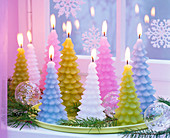 Pastel colored candles in fir tree shape on a light green tray by the window