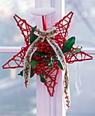 Ilex on a red wicker star, decorated with a ribbon with Ilex motifs