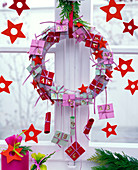 Advent calendar with pastel colored papers hung on a wreath in the window