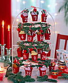 Advent calendar of small red buckets hung on a frame