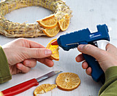 Gluing orange pieces to straw wreath