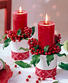 Ilex with red candles in white cups decorated with ribbon