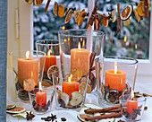 Orange candles in glasses filled with dried slices of malus