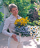 Young woman with myosotis (forget-me-not), Erysimum 'Gold'