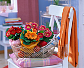 Red and orange gerberas in tissue paper in a metal basket