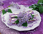 Syringa on white relief plate, napkin, cutlery, purple tablecloth