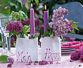 Purple candles in white paper bags with Syringa, Carpinus
