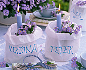 Myosotis in paper bags with blue candles as name tags