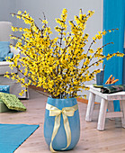 Bouquet of forsythia in turquoise egg vase with ribbon