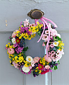 Door wreath from Bellis (daisies), Erysimum (gold paint), Prunus