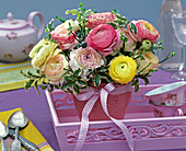 Bouquet of Ranunculus, Pittosporum in pink relief vase