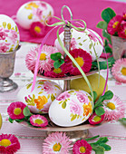 Bellis and painted eggs on silver etagere with ribbons