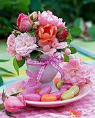 Small bouquet of different roses in egg cups on saucer