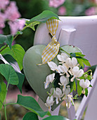 White dicentra on green metal heart on chair back