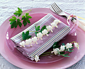 Dicentra on striped napkin on glass plate