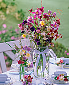 Aquilegia bouquet in preserving jar on covered tea table