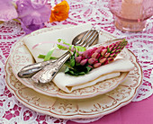 Lupinus on white cloth napkin, soup plate, place plate, cutlery