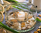 Mussels in glass bowl with white candle on checkered tablecloth
