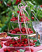 Etagere with prunus (cherries) and ribbons on the table, glasses