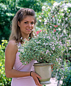 Young woman with Pelargonium fragans 'Variegatum' (scented geranium)