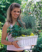 Young woman with basket full of freshly bought herbs