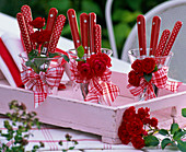 Rose on glasses with red cutlery and ribbons on tray