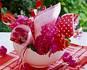 Pelargonium in bowl with rolled napkins with cutlery