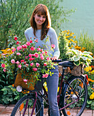 Young woman on bicycle holding pink (rose) and hosta (funkie)