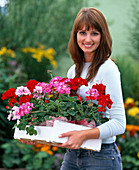 Young Woman with Pelargonium (Geranium) in White Orchid