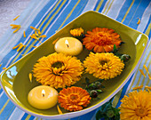 Calendula flowers and floating candles in a square bowl