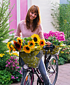 Woman bringing Helianthus and Phlox, in the background