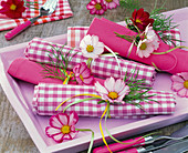 Cosmos on checkered and colored napkins on tray