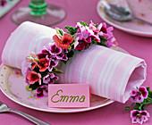 Pelargonium napkin ring around napkin, name tag 'Emma'