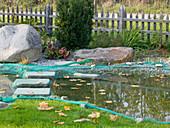 Teich im Herbst mit Netz abgedeckt zum Schutz vor Laub