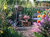 Seating in the cottage garden next to wooden rain barrel