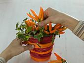 Ornamental paprika arrangement in cachepot from bast