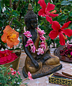 Buddha figure with a threaded chain of pink flower petals