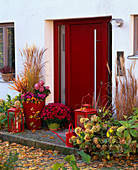 Roter Hauseingang herbstlich dekoriert mit Miscanthus