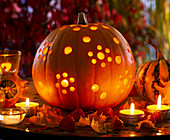 Cucurbita with punched holes as a lantern, autumn leaves