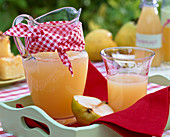 Freshly squeezed juice from Pyrus in pitcher with 'belly bandage' and in the glass