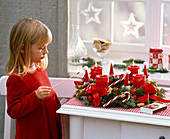 Girl lights candles on Advent wreath with Juniperus, Abies