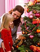 Mutter und Tochter vor Abies nordmanniana (Nordmanntanne) als Weihnachtsbaum